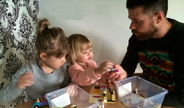 Dad and daughters at a desk learning about lego