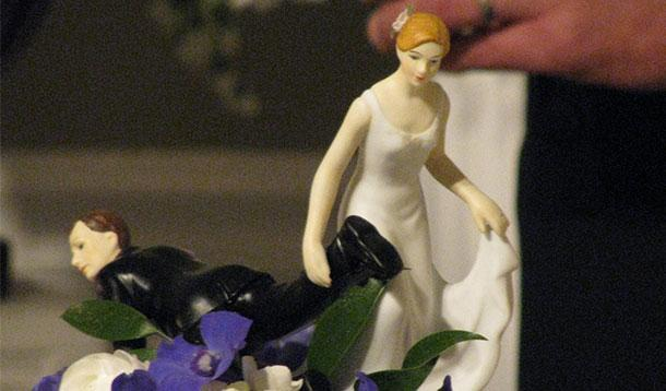 Bride dragging her groom to the alter but it's a cake topper.