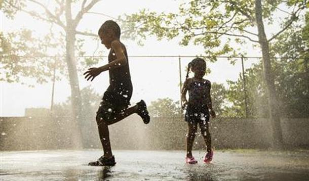 children playing in sprinkler
