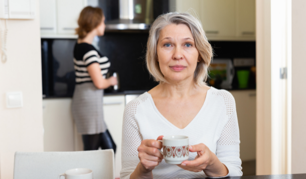 Mother in kitchen sitting at table with daughter in the background
