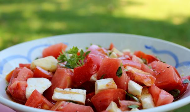 Ripe tomatoes and brie drizzled with hot olive oil and dressed with basil make for a delicious summery salad