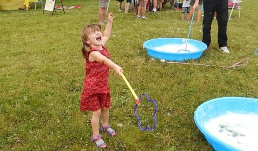 Joe's daughter rocking out with giant bubble wands