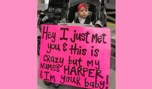 baby with welcome home sign