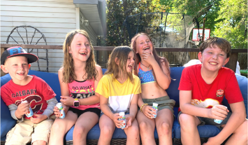 Kids laughing while sitting on a bench