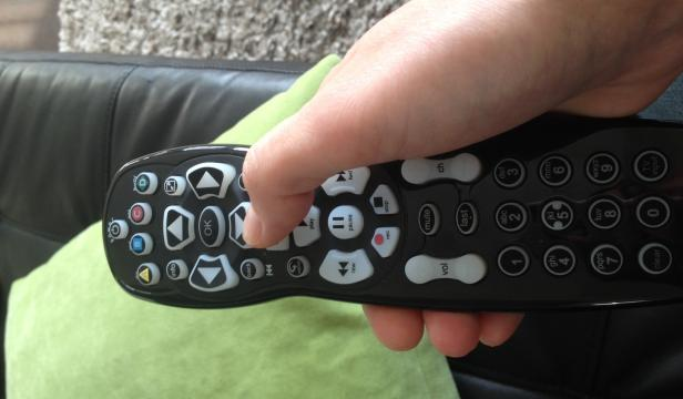 Woman's hand holding remote control