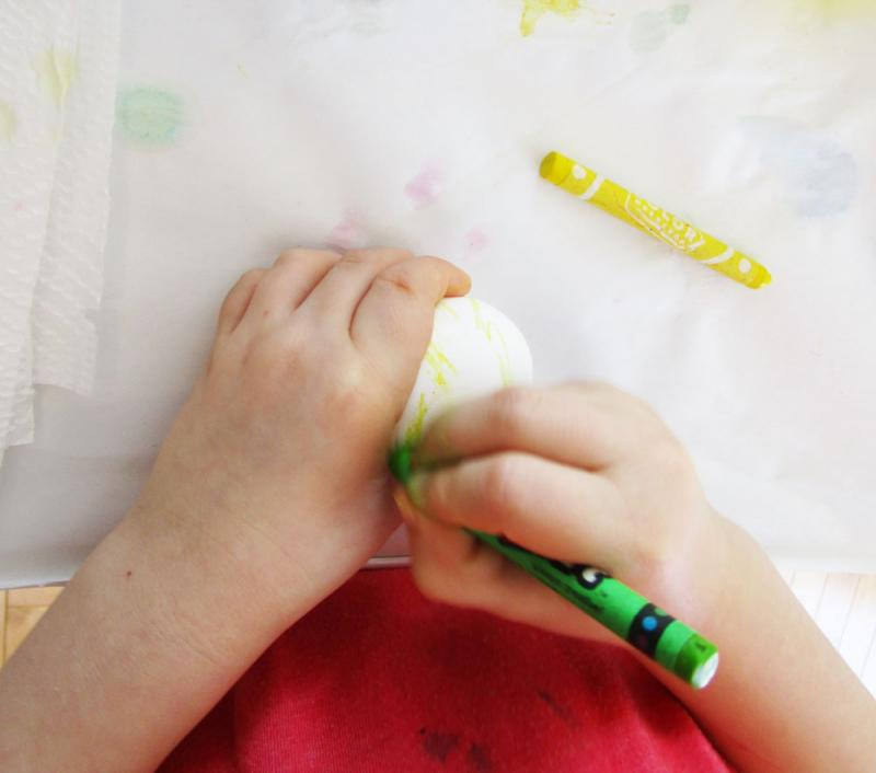 Use a light coloured crayon to make designs on an egg.