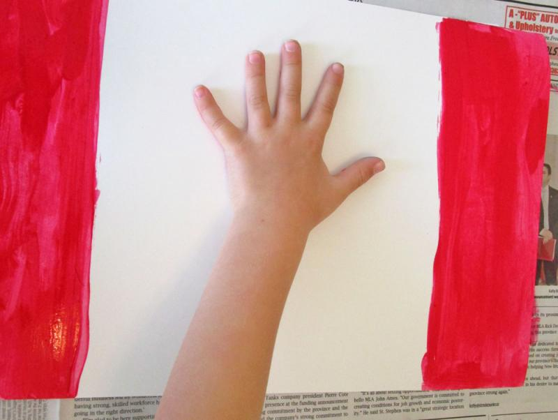 Place the hand on the paper - painted side down.