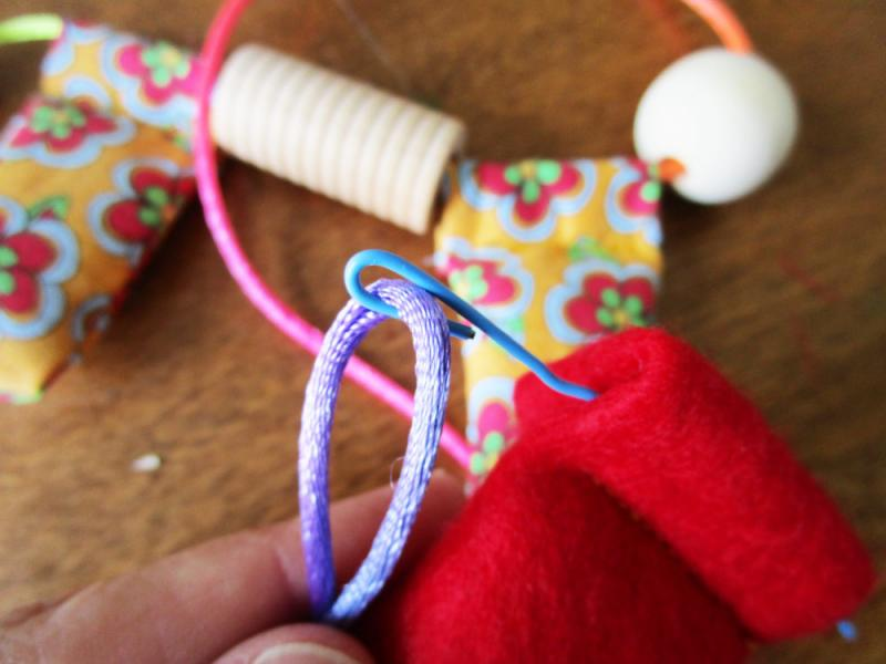 Use a paperclip to thread the fabric beads.