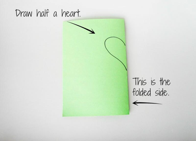 Draw half of a heart shape on the folded side of the paper.